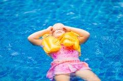 Fille adorable avec le gilet de vie jaune dans la piscine en plage tropicale au sujet de Photographie stock