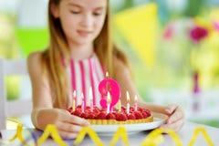 Fille adorable ayant la fête d'anniversaire à la maison, soufflant des bougies sur le gâteau d'anniversaire Image libre de droits