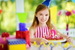 Fille adorable ayant la fête d'anniversaire à la maison, soufflant des bougies sur le gâteau d'anniversaire Photographie stock libre de droits