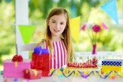 Fille adorable ayant la fête d'anniversaire à la maison, soufflant des bougies sur le gâteau d'anniversaire Photographie stock