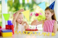 Fille adorable ayant la fête d'anniversaire à la maison, soufflant des bougies sur le gâteau d'anniversaire Images libres de droits