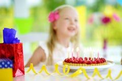 Fille adorable ayant la fête d'anniversaire à la maison, soufflant des bougies sur le gâteau d'anniversaire Photo stock