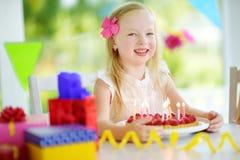Fille adorable ayant la fête d'anniversaire à la maison, soufflant des bougies sur le gâteau d'anniversaire Image stock