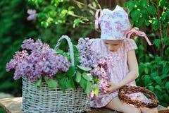 Fille adorable d'élève du cours préparatoire dans la robe rose de plaid faisant le jardin ensoleillé lilas de guirlande au printe Photo stock