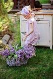 Fille adorable d'enfant dans la robe rose de plaid près du bureau de vintage avec des lilas dans le panier Photo stock