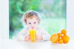 Fille adorable d'enfant en bas âge buvant du jus d'orange photos libres de droits