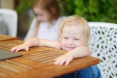 Fille adorable d'enfant en bas âge dans un restaurant extérieur Photos libres de droits