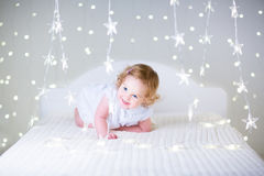Fille adorable d'enfant en bas âge entre les lumières de Noël Photographie stock libre de droits