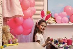 Fille adorable d'enfant en bas âge jouant avec des oeufs de pâques photographie stock