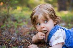 Fille adorable d'enfant en bas âge se trouvant au sol avec elle réceptrice Image stock