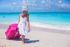 Fille adorable dans le chapeau et des mitaines chauds d'hiver marchant avec le bagage sur la plage Photographie stock libre de droits