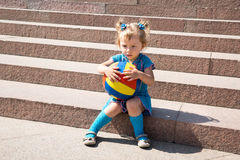 Fille adorable de petit enfant avec la boule de jouet sur des escaliers Image stock