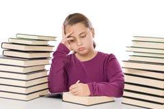 Fille adorable fatiguée avec beaucoup de livres image stock