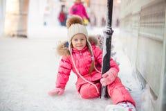 Fille adorable heureuse s'asseyant sur la glace avec des patins Images stock