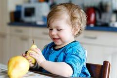 Fille adorable mignonne d'enfant en bas âge mangeant la poire fraîche Enfant heureux affamé de bébé d'un an tenant le fruit Photos libres de droits