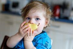 Fille adorable mignonne d'enfant en bas âge mangeant la poire fraîche Enfant heureux affamé de bébé d'un an tenant le fruit Photographie stock libre de droits