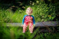 Fille adorable mignonne d'enfant en bas âge s'asseyant sur le pont en bois et les petites pierres de lancement dans une crique Bé photo stock