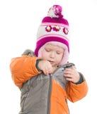 Fille adorable rectifiant la jupe et le chapeau de l'hiver Image stock