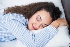 Fille adulte mignonne souriant dans son sommeil Photographie stock libre de droits