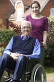 Fille adulte poussant le père In Wheelchair Photo libre de droits