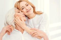 Fille affectueuse étreignant sa maman supérieure à la maison Image stock