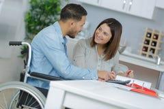 Fille affectueuse avec l'ami dans le fauteuil roulant Photographie stock libre de droits