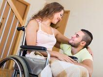 Fille affectueuse dans le fauteuil roulant avec son ami Image libre de droits