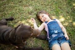 Fille affectueuse jouant avec le chien Image libre de droits