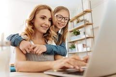 Fille affectueuse observant sa mère travailler Photos stock
