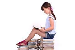 Fille affichant booksitting sur la grande pile des livres Images libres de droits