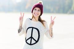 Fille affichant le signe de paix Photos stock