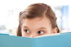Fille affichant un livre à l'école Photographie stock libre de droits