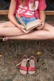 Fille affichant un livre sur un banc Images libres de droits