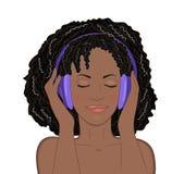 Fille africaine avec des yeux fermés et un sourire écoutant la musique dans des écouteurs sur le fond blanc Photographie stock libre de droits