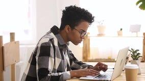 Fille africaine contrariée d'étudiant d'appartenance ethnique dactylographiant regardant l'écran d'ordinateur banque de vidéos