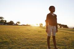 Fille africaine d'école primaire se tenant en parc au coucher du soleil images stock