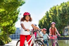 Fille africaine faisant un cycle avec des amis au parc de ville Images libres de droits