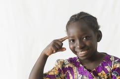 Fille africaine magnifique dirigeant le doigt à sa tête, d'isolement sur W photographie stock libre de droits