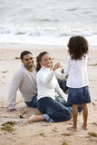 Fille afro-américaine avec des parents sur la plage photographie stock