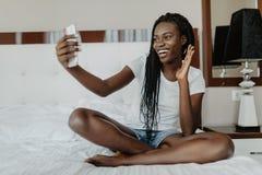 Fille afro-américaine de métis gai ayant la causerie visuelle avec des amis à l'aide de la caméra d'ordinateur portable tout en s photo libre de droits