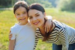 Fille agréable et mère gaies souriant à l'appareil-photo Photos stock