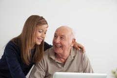 Fille aidant à son grand-père avec l'ordinateur Photographie stock libre de droits