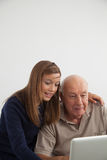 Fille aidant à son grand-père avec l'ordinateur Image stock
