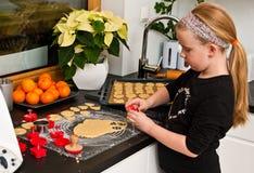Fille aidant avec la cuisson de Noël de gingembre Images libres de droits
