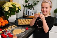 Fille aidant avec la cuisson de Noël de gingembre Image stock