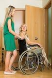 Fille aidant la femme handicapée Photos stock
