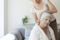 Fille aidant la mère malade avec le foulard photographie stock libre de droits