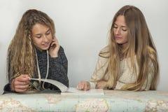 Fille aidant la petite soeur avec son travail au-dessus d'une carte de table Images libres de droits