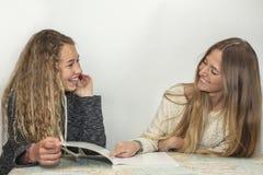 Fille aidant la petite soeur avec son travail au-dessus d'une carte de table Image stock
