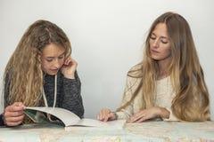 Fille aidant la petite soeur avec son travail au-dessus d'une carte de table Photos stock